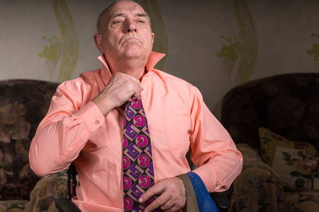 oldage: Handsome senior man is trying on a beautiful tie