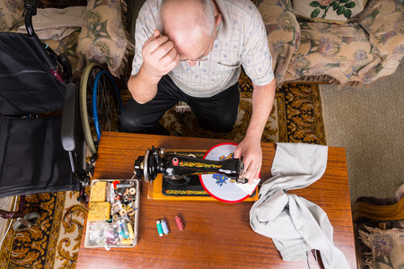 oldage: High Angle View of Senior Man Working on Needle Point Wall Hanging Craft Using Old Fashioned Manual Sewing Machine at Home in Living Room