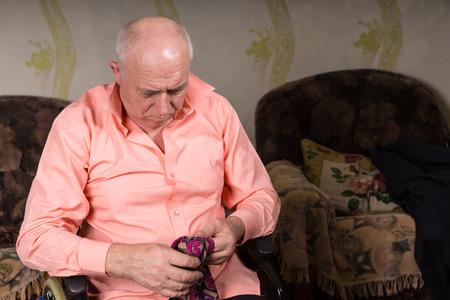 natty: Senior sad man looking on his tie