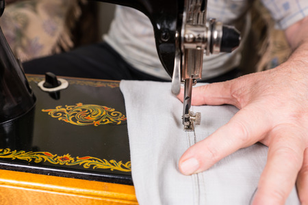 mending: Close Up View of Senior Man Mending Pants with Old Fashioned Ornate Sewing Machine