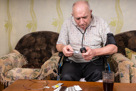 special needs: Bald Elderly Man with Special Needs Sitting on his Wheelchair Inside his House, Reading a Sphygmomanometer While Holding his Medicine.