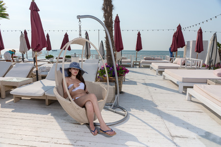 upmarket: Young woman relaxing on a seaside vacation at an upmarket resort relaxing on the seashore in a modern bath chair in her straw sunhat and bikini