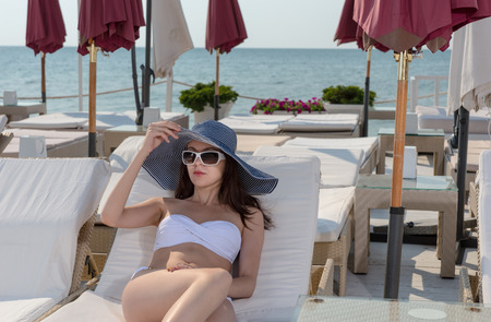recliner: Fashionable young woman sunbathing in a bikini as she relaxes at a coastal resort on a recliner chair wearing trendy sunglasses and sunhat Stock Photo