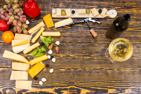 High Angle View of Gourmet Cheeses and Fresh Fruits with Glass of White Wine and Bottle on Rustic Wooden Table with Central Copy Space Archivio Fotografico