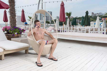 oceanfront: Full Length of Young Man in Bathing Suit Making Call on Cell Phone While Relaxing in Wicker Deck Chair on Patio of Oceanfront Luxury Vacation Resort