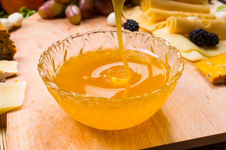 tabla de quesos: Pouring healthy golden honey into a round glass bowl on a table for use as a dip and spread