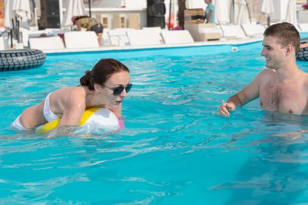 Young Couple Playing with Beach Ball in the Swimming Pool of a Resort on a Tropical Climate.