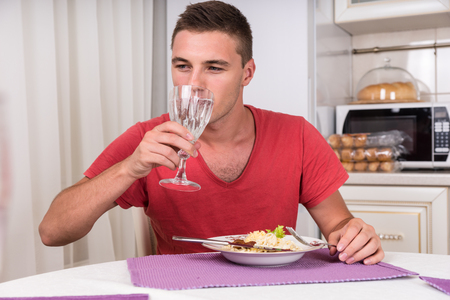 sip: Young Man Taking Sip of Water During Dinner of Home Cooked Pasta While Seated at Dining Table in Quaint Kitchen