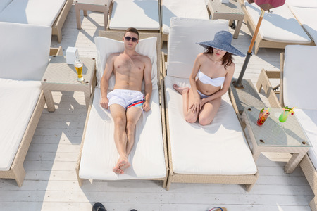 recliner: Young couple enjoying a lazy day in the sunshine as they relax on recliner chairs at a seaside resort in the tropics on their summer vacation Stock Photo