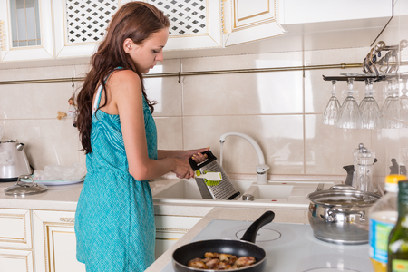 cooking implement: Woman washing a cheese grater under running water in the kitchen sink after grating cheddar cheese for the recipe she is preparing Stock Photo
