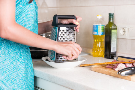 grating: Woman grating cheese on a grater to use as an ingredient in her cooking as she prepares a meal