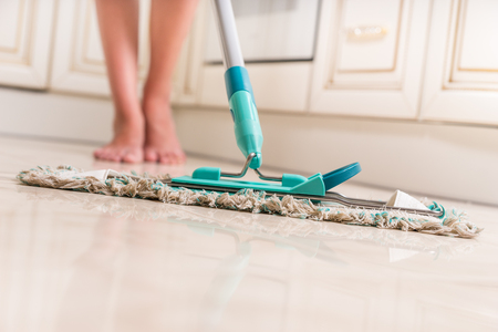 young girl feet: Low Angle View of Young Woman Mopping Kitchen Floor with Focus on Shiny Clean Floor and Mop