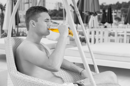 oceanfront: Profile of Young Man Relaxing in Wicker Chair with Tall Glass of Cold Beer on Deck of Oceanfront Luxury Vacation Resort