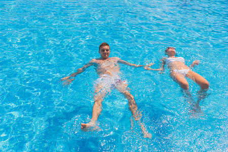 backs: Young Relaxed Couple Floating Side by Side on Backs in Clear Water of Resort Swimming Pool on Sunny Day
