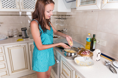 home cooked: Young Brunette Woman Sprinkling Grated Cheese on Pasta in Pot While Preparing Home Cooked Meal for Dinner in Kitchen
