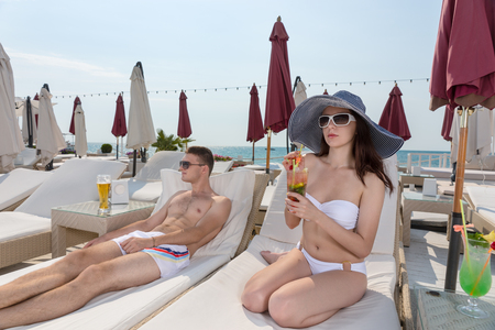 Young Couple with Tropical Drinks Relaxing on Lounge Chairs on Sunny Deck of Oceanfront Luxury Beach Resort Stock Photo
