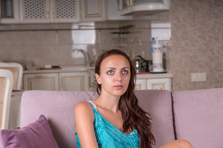 intent: Close Up of Young Brunette Woman Staring Into Space or Watching Television with Blank Expression While Sitting on Sofa at Home