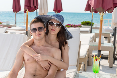oceanfront: Portrait of Young Couple with Arms Around Each Other Sitting Together on Lounge Chair with Tropical Drink on Sunny Deck of Oceanfront Luxury Beach Resort