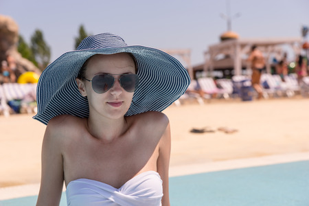 expressionless: Waist Up Close Up of Young Woman on Vacation Wearing Sun Hat, Sunglasses and White Bikini While Sitting on Sunny Deck of Public Resort Swimming Pool
