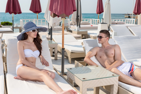 oceanfront: Young Couple on Vacation Having Relaxing Conversation on Lounge Chairs on Oceanfront Luxury Beach Resort