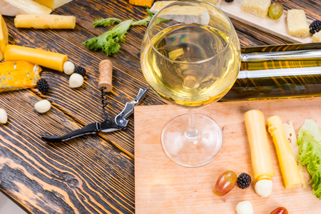 unlabelled: High Angle View of Glass of White Wine on Rustic Wooden Table Surrounded by Cheeses and Fruit for Gourmet Cheese Board Stock Photo