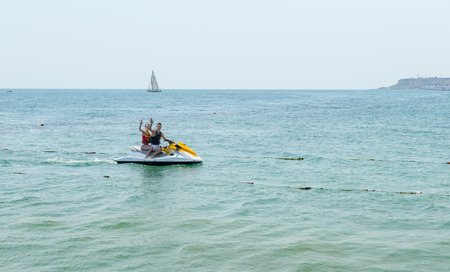 idling: Young couple waving from a jet ski mid ocean as they enjoy some recreational water sport on their summer vacation