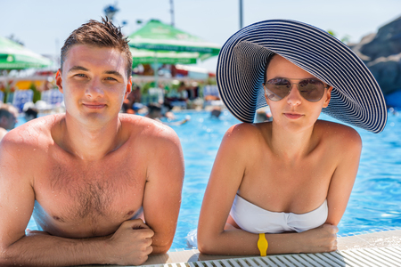 Portrait of Young Couple on Vacation Leaning on Edge of Swimming Pool on Hot Sunny Day - Young Man and Woman Enjoying Summer Sun While Relaxing in Pool