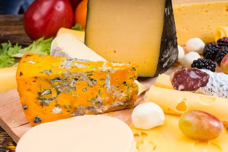 tabla de quesos: Cerca de la placa de queso gourmet con variedad de quesos, carnes curadas y adornado con la fruta fresca