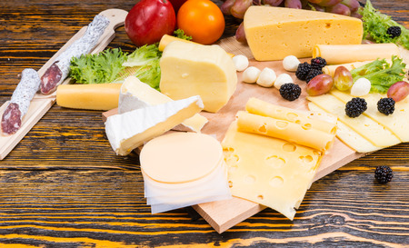tabla de quesos: High Angle View of Gourmet Cheese Board Featuring Variety of Cheeses, Cured Meats and Fresh Fruit Served on Rustic Wooden Table with Wood Grain and Copy Space Foto de archivo