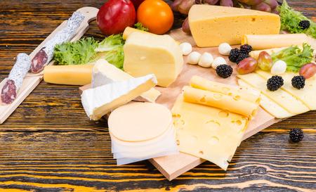 tabla de quesos: Opinión de alto ángulo de la Junta de queso gourmet cuenta con variedad de quesos, embutidos y fruta fresca servida en mesa de madera rústica con madera del grano y el Espacio