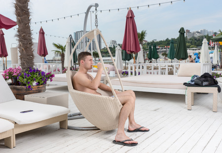 oceanfront: Profile of Young Man in Swim Suit Relaxing in Wicker Chair with Tall Glass of Cold Beer on Deck of Oceanfront Luxury Vacation Resort