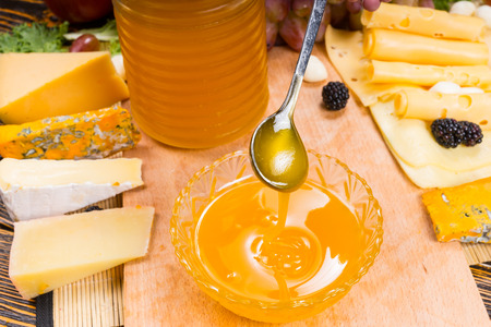 tabla de quesos: Pouring honey into a bowl on a cheese platter with a large assortment of different cheeses on the side to be used as a healthy dip