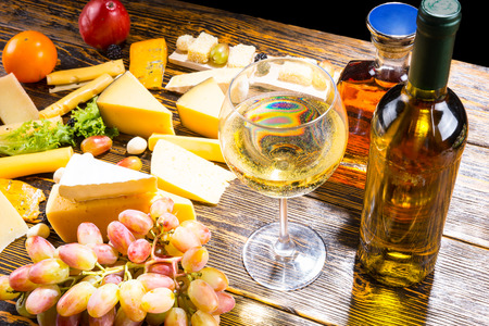 botella de whisky: High Angle View of Glass of White Wine on Rustic Wooden Table with Bottles, Variety of Cheeses and Fresh Fruits