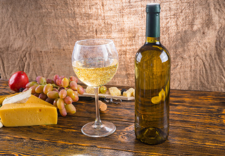 unlabelled: Gourmet Food Still Life - Close Up of White Wine in Glass Next to Bottle on Rustic Wooden Table with Cheese and Grapes