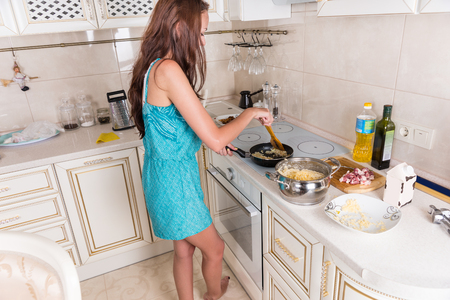 sautee: Young woman preparing savory meat and spaghetti standing at the stove stirring the meat in the frying pan surrounded by fresh ingredients Stock Photo