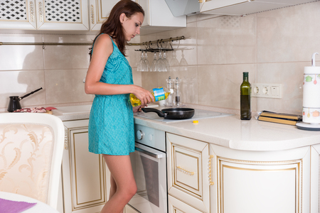sautee: Young Woman Putting Oil on a Frying Pan Placed on Top of the Burner Stove in the Kitchen. Stock Photo