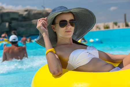 summer vacation bikini: Close Up of Young Woman on Vacation Wearing Sun Hat, Sunglasses and White Bikini Relaxing in Bright Yellow Inner Tube in Public Swimming Pool at Water Park Resort on Sunny Summer Day
