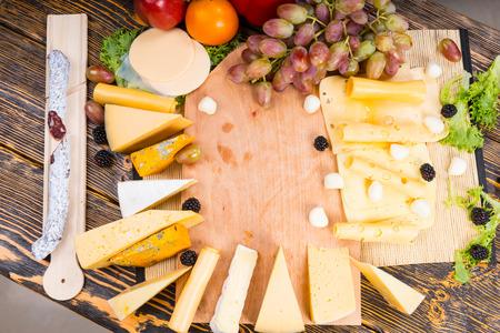 tabla de quesos: Gran variedad de quesos que se muestran alrededor de una tabla de quesos de madera con uvas frescas, tomate y chorizo ??en el lado, vista aérea con copyspace centro Foto de archivo