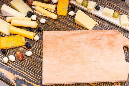 caterers: High Angle View of Wooden Board Surrounded by Variety of Gourmet Cheeses and Fresh Fruit on Rustic Wooden Table with Wood Grain and Copy Space