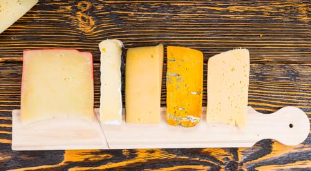 tabla de quesos: Tabla de quesos con una variedad de quesos dispuestos sobre una mesa de buffet en una fila ordenada en una mesa de madera rústica en un evento atendido