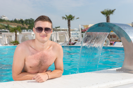 surround: Attractive young man relaxing in a resort swimming pool standing leaning on the tiled surround smiling at the camera alongside a fountain feature of curved metal
