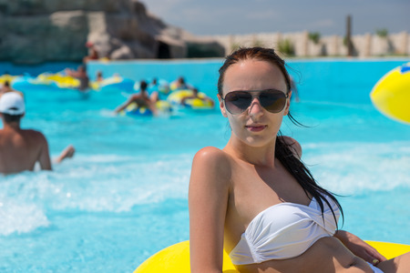 Close Up of Young Woman on Vacation Wearing Sunglasses and White Bikini Relaxing in Bright Yellow Inner Tube in Public Swimming Pool at Water Park Resort on Sunny Summer Day Stock Photo