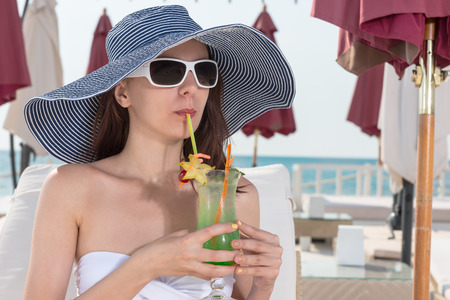 sunhat: Elegant young woman sipping an ice cold fruit cocktail as she relaxes at the beachfront in a trendy wide brimmed sunhat and sunglasses