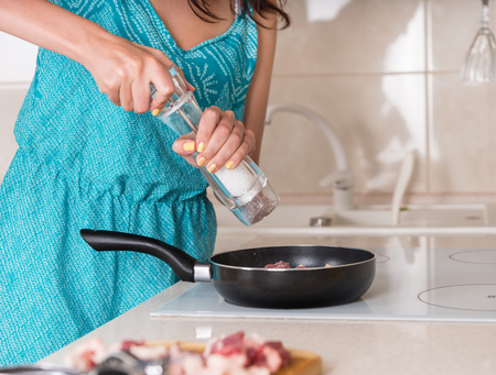 Woman grinding salt from a salt mill into a frying pan as she cooks the dinner, close up of her hands and the pan 스톡 콘텐츠