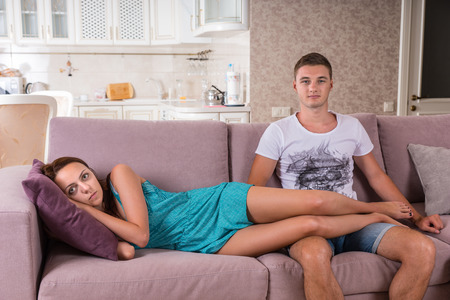 woman lying down: Young Couple Watching Television Together on Sofa - Woman Lying Down Relaxing with Feet Up on Lap of Man