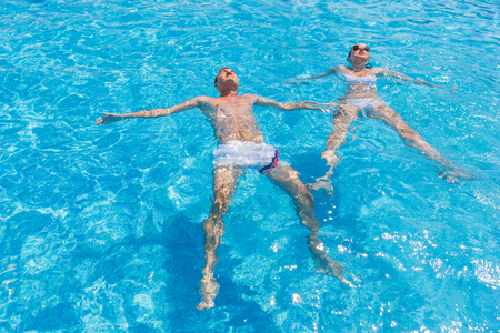 Young Relaxed Couple Floating Side by Side on Backs in Clear Water of Resort Swimming Pool on Sunny Day