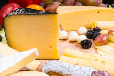 tabla de quesos: Hasta cerca de Cheese Board Gourmet cuenta con variedad de quesos, carne curada y adornado con la fruta - Detalle de la Junta de queso apetitoso Foto de archivo