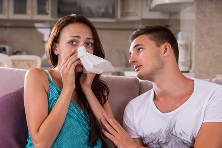 comforted: Tearful young woman being comforted by her caring boyfriend or partner as she dries her eyes with a handkerchief, head and shoulders view on a sofa Stock Photo