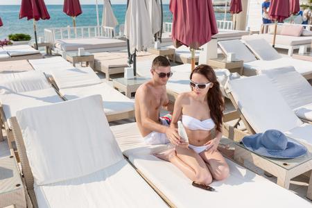 clima tropical: Gentleman Ayudar a su novia pone la protección solar Loción mientras está sentado en las tumbonas en el Resort en un clima tropical.