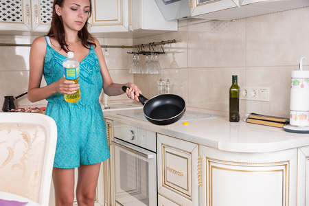 sautee: Young Woman at the Kitchen, Holding the Frying Pan While Spreading the Oil.